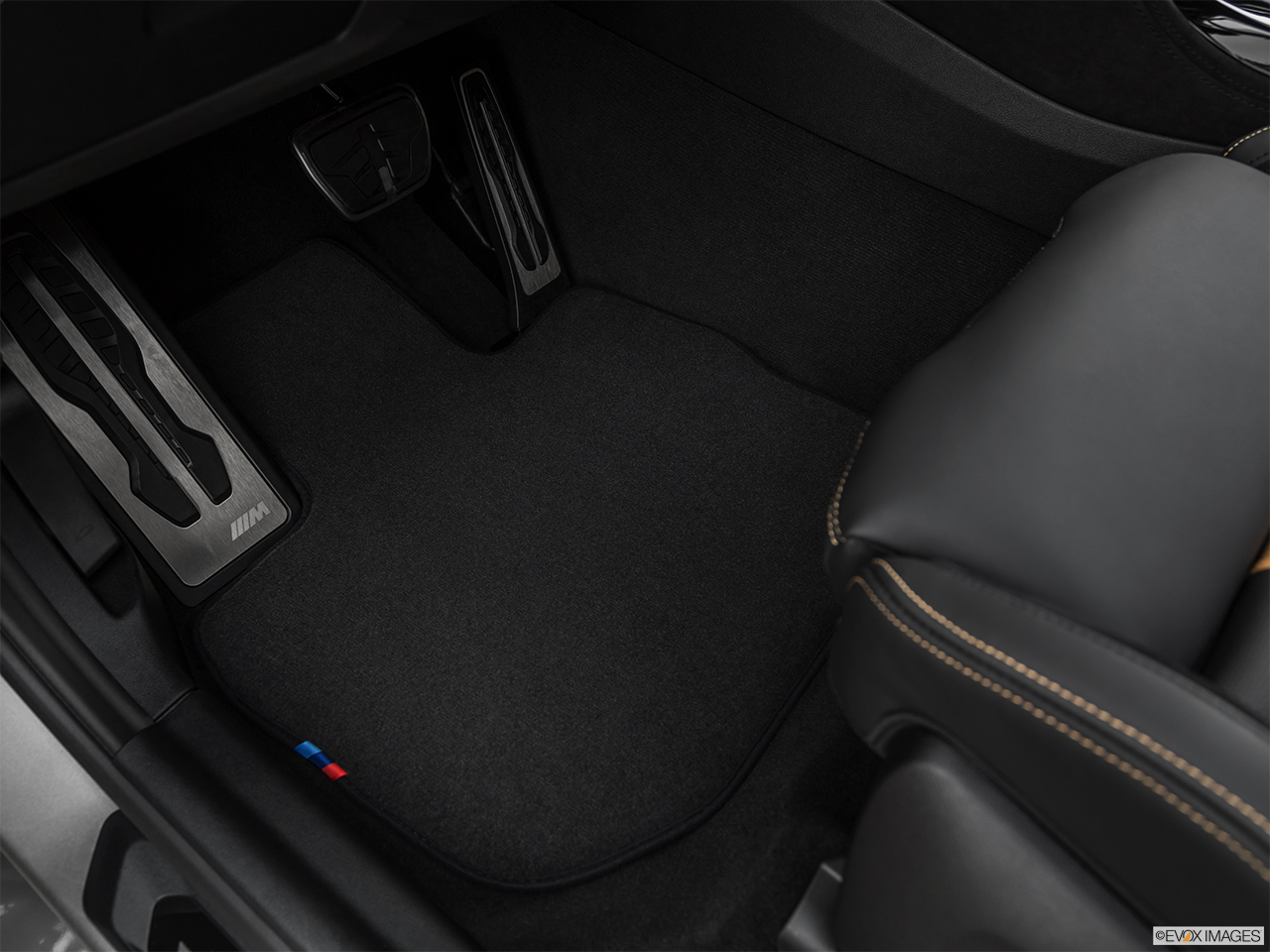 2020 BMW X3 M Competition Driver's floor mat and pedals. Mid-seat level from outside looking in.