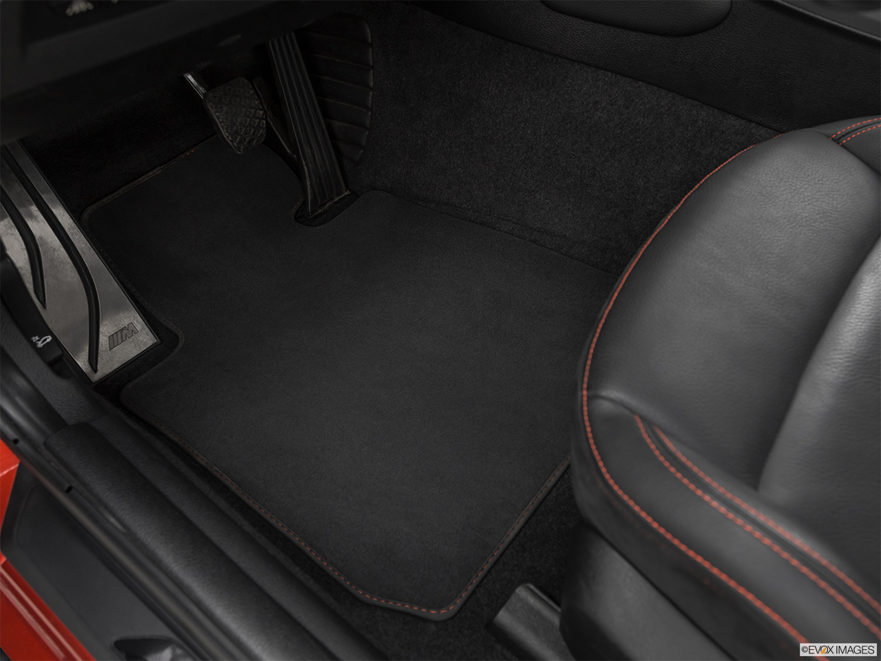 2020 BMW M2 Competition Driver's floor mat and pedals. Mid-seat level from outside looking in.